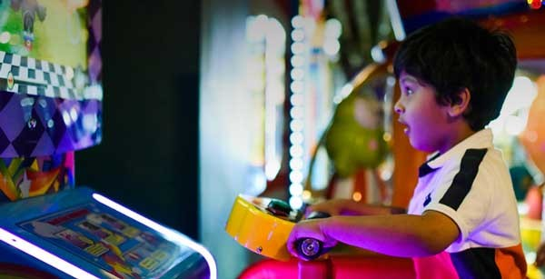 kid playing arcade game